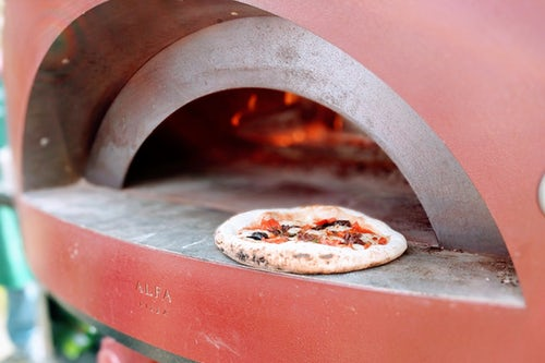 Pizza Dishes Being Prepared in Stone Oven