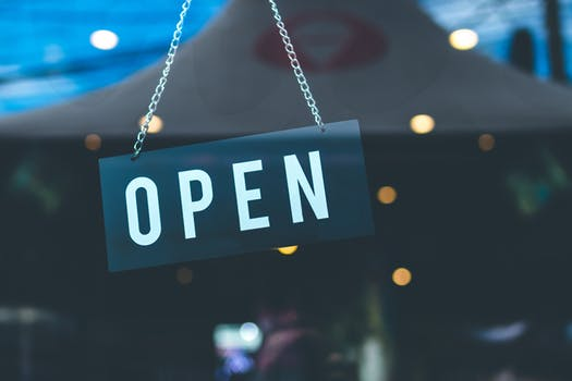 "An ""Open"" sign hanging on a chain is one that is commonly found in restaurants in London"